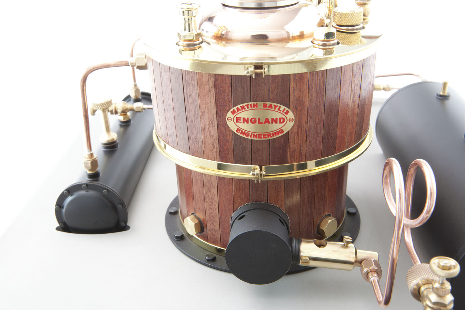 The model boiler features wooden cladding and brass bands. The ceramic burner and quick release gas fitting can be seen. Visible is the simulated flanged and bolted end to the separator tank adding an additional note of authenticity.