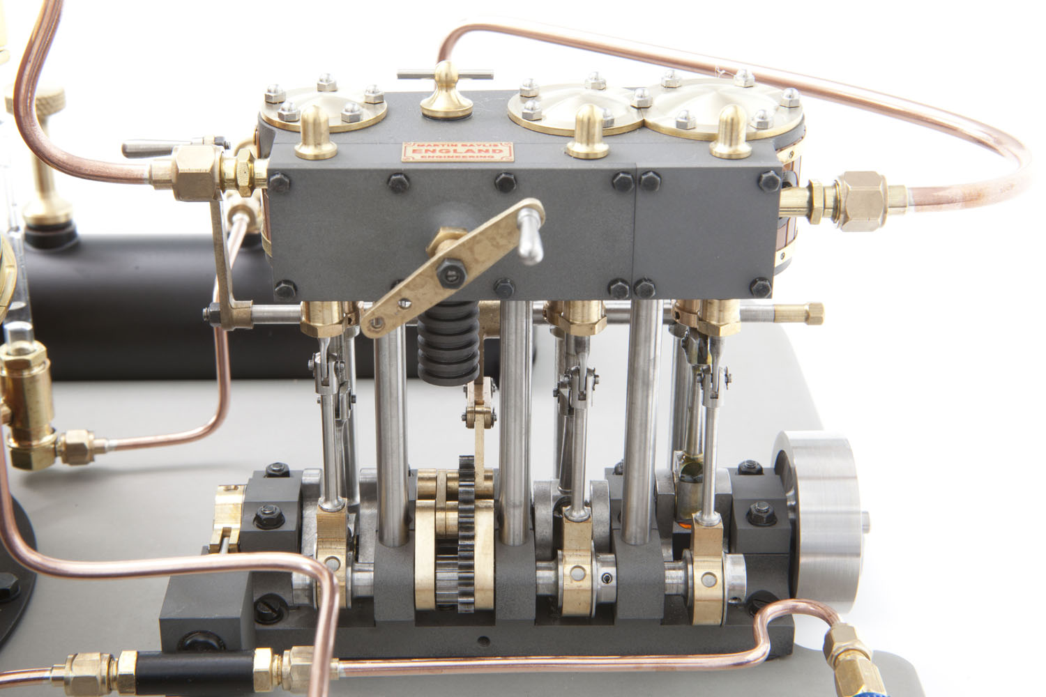 The three-cylinder model engine together with the engine driven feed pump and various sections of copper pipework.